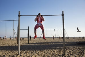 Fitness instructor Darren Gumbs works out on the beach wearing a bodysuit showing the human muscular system, Santa Monica, California, US