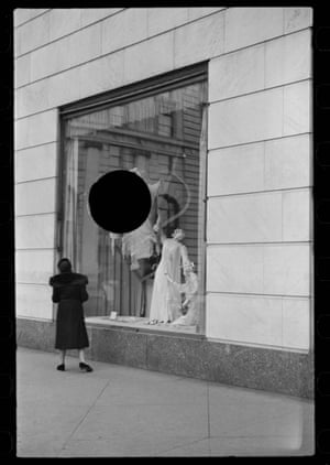 Woman looking at window display with black circle hovering in centre of window