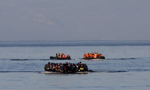 Three dinghies overcrowded with migrants and refugees approach a beach on the Greek island of Lesbos after crossing a part of the Aegean Sea from Turkey.