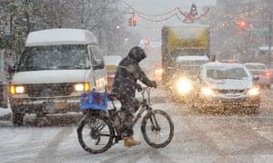 A cyclist gingerly crosses a snowy road in Brooklyn, New York, last week.