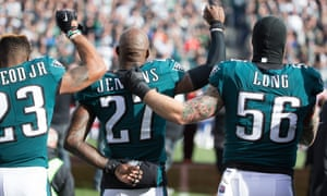 Rodney McLeod, Chris Long and Malcolm Jenkins of the Philadelphia Eagles raise their fists during a game.