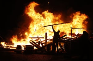 A protestor adds wood to a fire on the Champs-Elysees in the heart of the French capital.