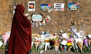 A woman stops to read tributes for the victims of the van attack