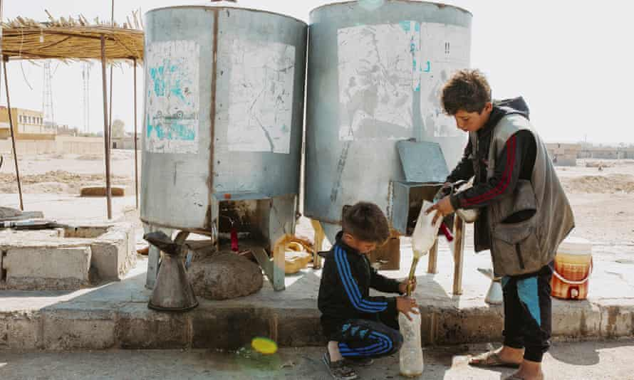Two young boys working at a petrol station near the town of Shaddadi in Hasakah province.