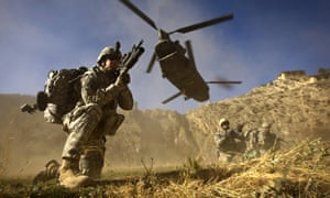 US soldiers take position as a helicopter flies overhead in Khost province, Afghanistan