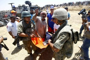 A female Syrian refugee is carried by Turkish soldiers to an ambulance after crossing into Turkey near Akçakale