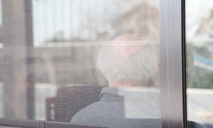 older person sits behind a window