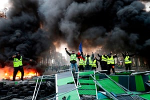 Black smoke billows as Yellow vests (Gilets jaunes) protestors shout slogans.
