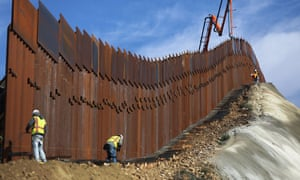 A construction crew works on new sections of the US-Mexico border barrier.