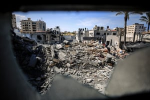 Palestinians inspect a demolished building after Israeli warplanes hit Rimal neighbourhood in Gaza City