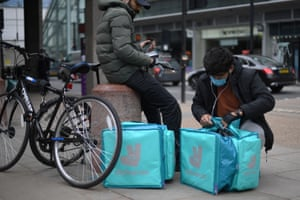 A Deliveroo rider packing take-away meals into his bag, near Victoria Station in central London earlier this month.