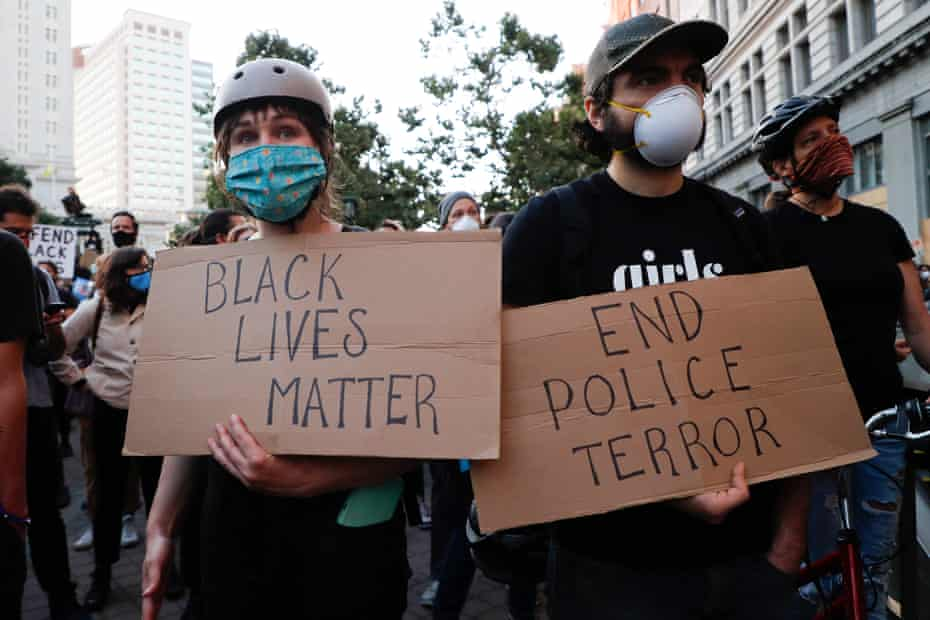 """People hold signs reading """"Black Lives Matter"""" and """"End police terror"""" during a protest in Oakland, California, on 3 June 2020."""
