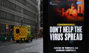 An ambulance passing a Covid public health notice in London today.