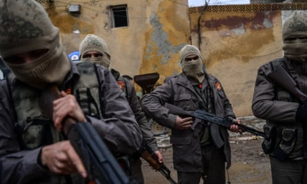 Turkish-backed Syrian rebel fighters patrol the streets in the Afrin enclave.