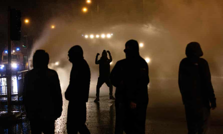 Police officers using water cannon as they clashed with nationalist youths in the Springfield Road area of Belfast on Thursday.