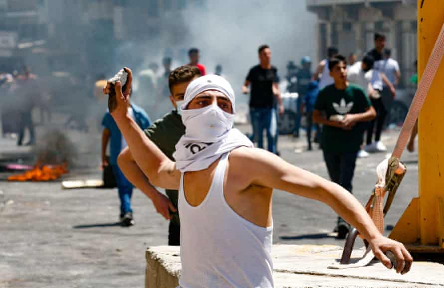 A Palestinian youth hurls rocks toward Israeli security forces, during confrontations with them in the occupied West Bank city of Hebron, on May 14, 2021. Photo by Hazem Bader/AFP