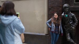 Visitors take photographs next to a statue of John Lennon in Matthew Street, Liverpool
