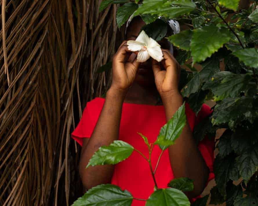 In bright red dress in undergrowth holding flower to cover face