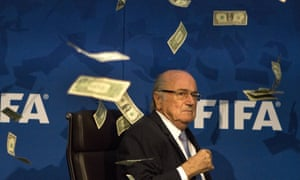 FIFA president Sepp Blatter is showered with banknotes by a prankster during a press conference in 2015.