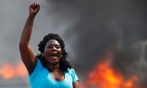A resident of Masiphumelele shouts at police while barricades burn behind her
