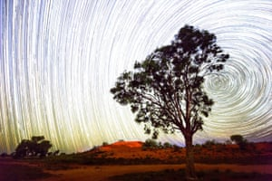 Star trails are seen over red sand dunes in the town of Windorah in the far south-west of Queensland.