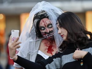 Women dressed in Halloween costumes pose for a selfie before participating in the zombie walk in Essen, Germany.