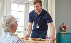 Male care worker serving dinner to a senior man