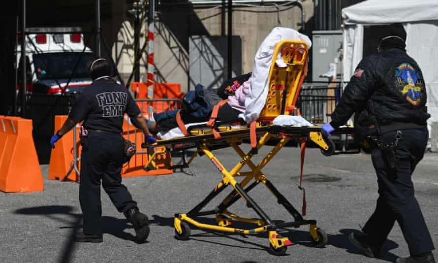 Paramedics roll a stretcher with a patient to Brooklyn hospital center emergency room on 27 March 2020 in New York City.