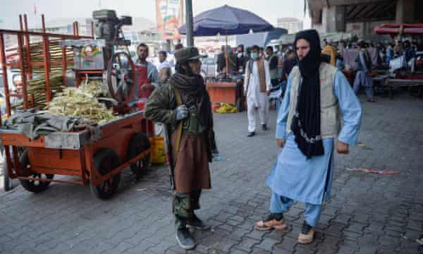 A Taliban fighter in a market in Kabul