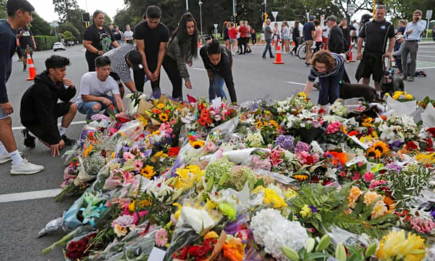 People place flowers at a memorial as a tribute to victims of the mosque attacks, near a police line outside Masjid Al Noor in Christchurch