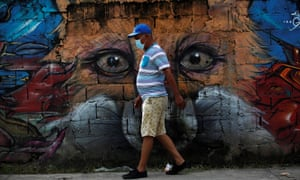 A resident walks with a face mask in front of a mural during a disinfection day in the Chorrillo neighborhood to combat the spread of the coronavirus, in Panama City, Panama, 30 June 2020.