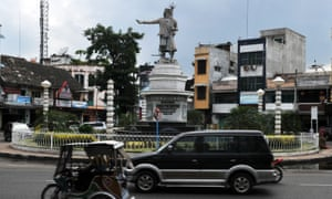 Motorists pass the Guru Patimpus statue in downtown Medan