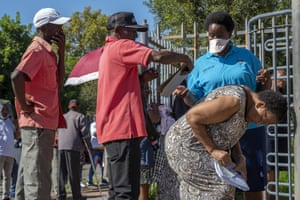 People seeking medical assistance queue outside a clinic in Soweto