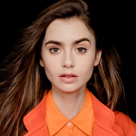 Lily Collins looking at camera wearing orange Christopher Esber