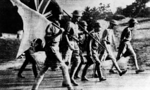 British forces, carrying union and white flags, surrender to the Japanese in Singapore in 1942.