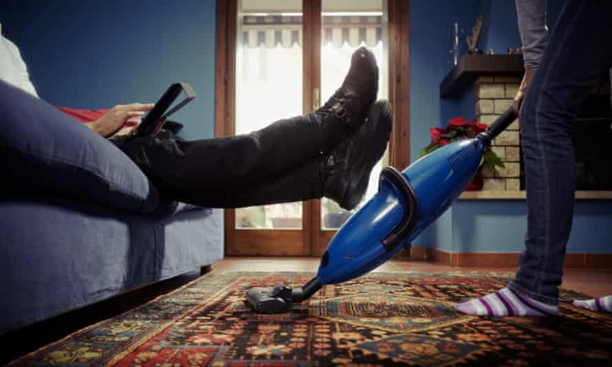 Woman using vacuum cleaner on carpet and man on sofa with tablet pc.