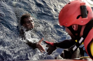 A migrant is rescued from the mediteranean sea by a member of Proactiva Open Arms NGO