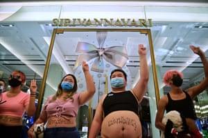 Demonstran memberi hormat tiga jari selama 'protes tanaman' di luar butik milik anggota keluarga kerajaan Thailand di Bangkok pada 20 Desember.