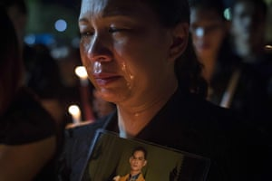 A mourner cries at a candlelit ceremony for late King Bhumibol Adulyadej at the Sanam Luang Park outside the Grand Palace in Bangkok, Thailand