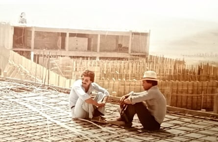 Anwar al-Bunni and another man, in 1982, sitting on part of the unfinished Saydnaya prison, which he helped build while working in construction before he began legal training.