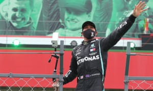 Lewis Hamilton waves to the spectators after winning the Portuguese Grand Prix, with the image of Michael Schumacher (top left) in the background.