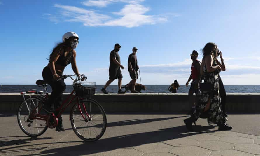 People exercise along the St Kilda beach promenade in Melbourne.