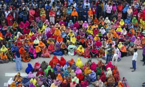 Bangladeshi garment workers block a road during a demonstration to demand higher wages in Dhaka