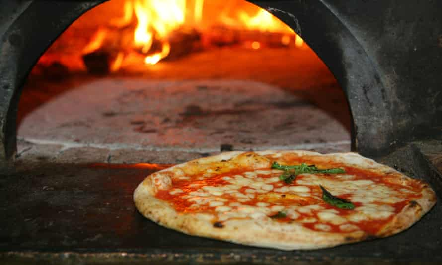 Neapolitan-style pizza in front of pizza oven