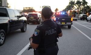 Police at the scene outside Marjory Stoneman Douglas high school in Parkland, Florida, where more than a dozen were killed.