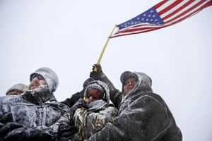 Military veterans and activists huddle together against the strong winds.