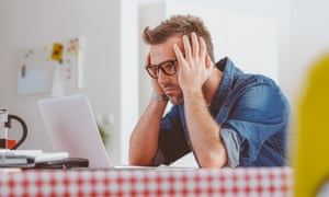 worried man looking at a laptop