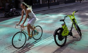 A cyclist passes a rental bike on the pavement. £2bn will be spent on cycling and walking across a five year period, under new plans.