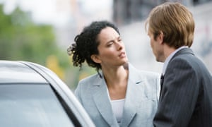 Businesswoman and man speaking next to car looking angry