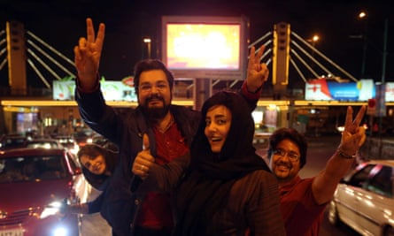 "People flash the ""V for Victory"" sign as they celebrate on Valiasr street in northern Tehran."